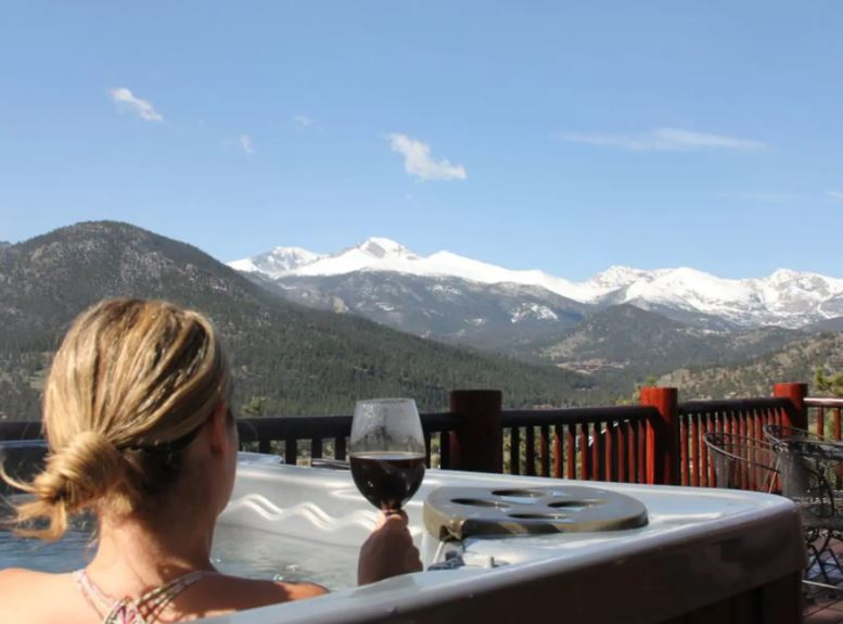 Woman drinking wine in a hot tub on a patio that over looks mountains near Estes Park Colorado