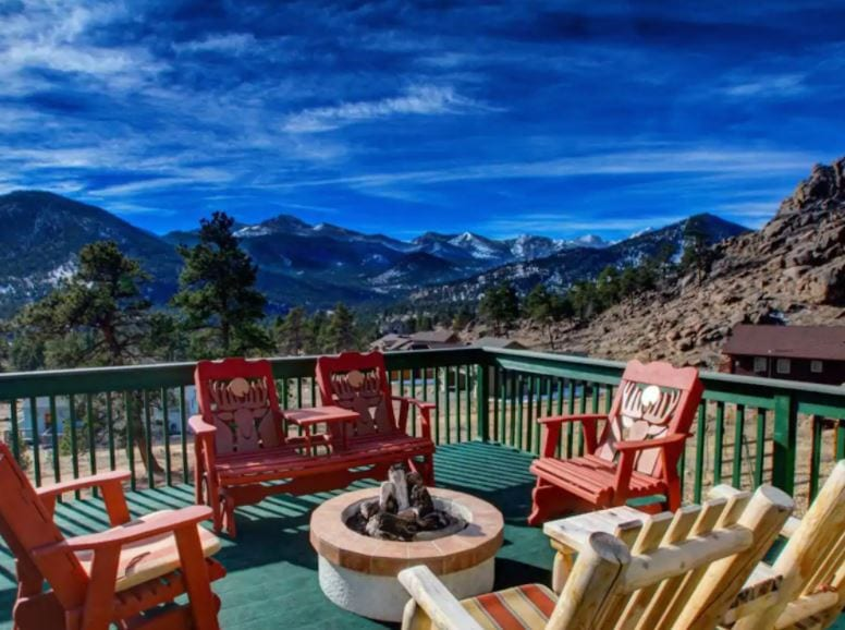 Estes Park Airbnb patio with mountain views and red patio chairs with a fire pit