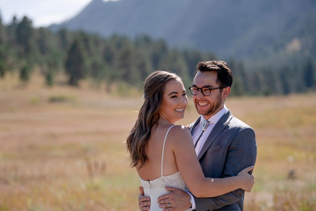 Bride and groom embracing each out and laughing at the Boulder Colorado elopement