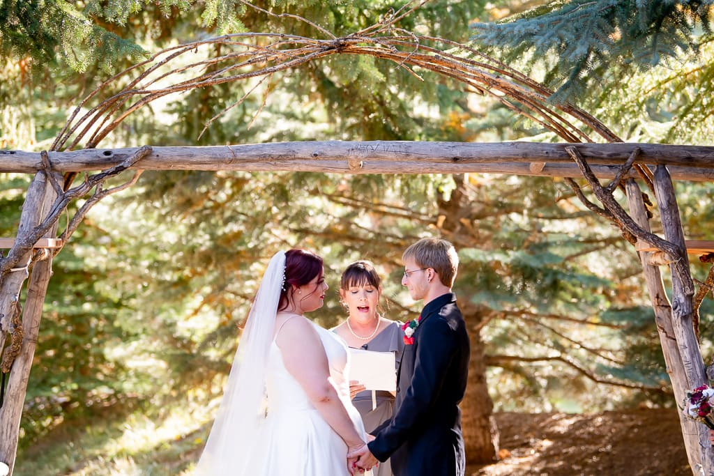 Bride and groom hold hands while officiant leads small wedding ceremony in front of trees and wooden arch