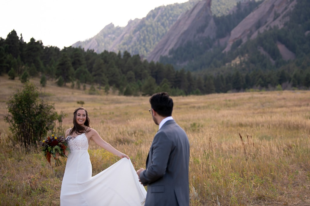 Groom looking at his smiling bride as she waves her dress in a field in Chautauqua Park in Boulder, Colorado