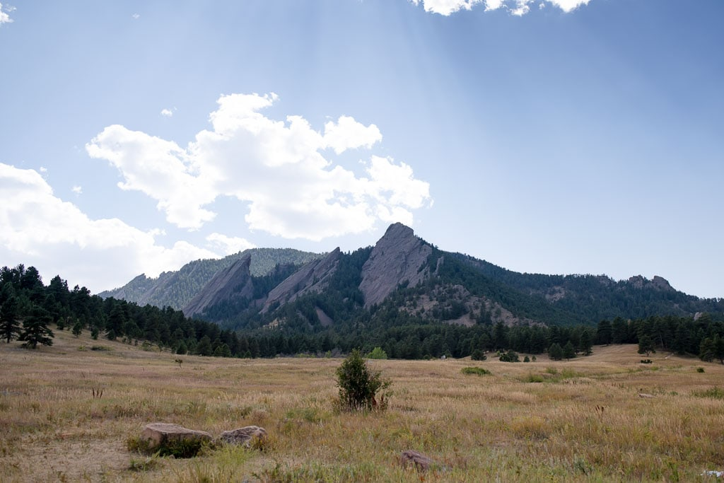Flatiron mountains on a sunny day with a few clouds and a field of yellow and green grass