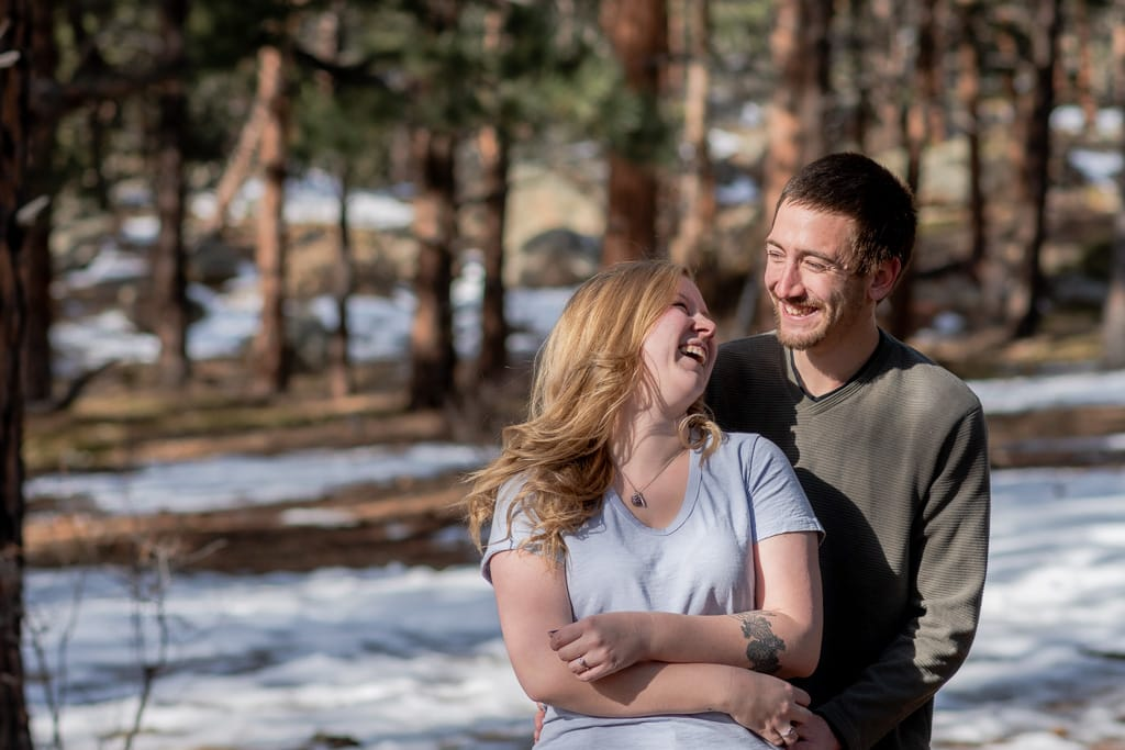 Engaged couple laughing with each other in a Colorado forest