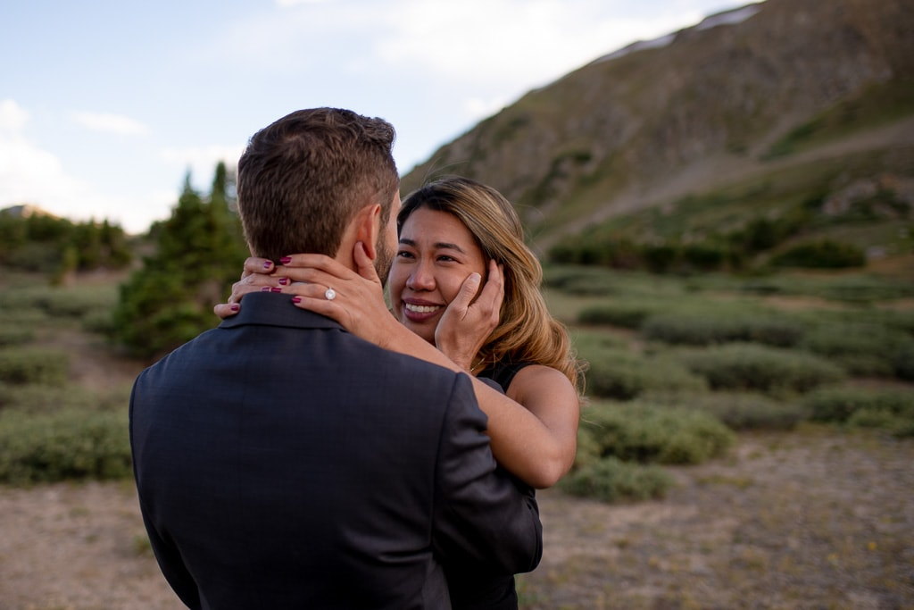 Bride crying happy tears while groom holds her as they stand in a green mountain setting near Breckenridge, Colorado