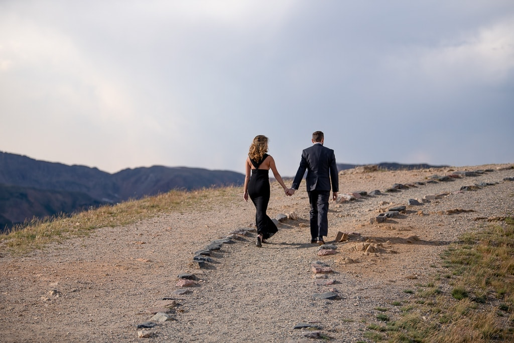 Bride in a black wedding dress holding groom's hand and walking up a mountain path
