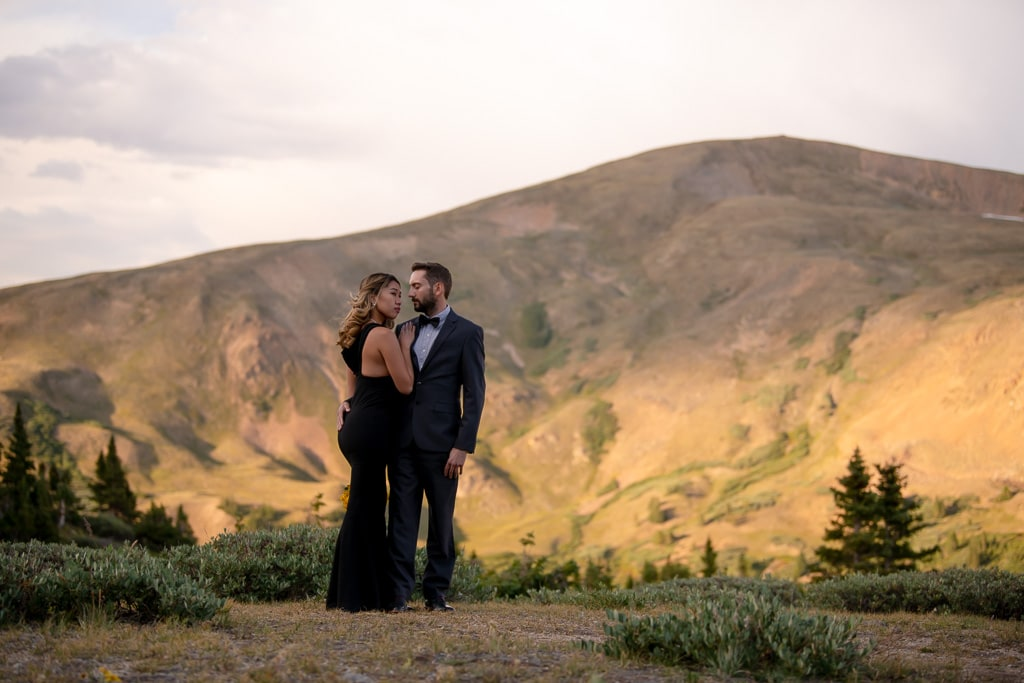 Bride in a black dress standing next to a groom in a tux with a mountain in the background