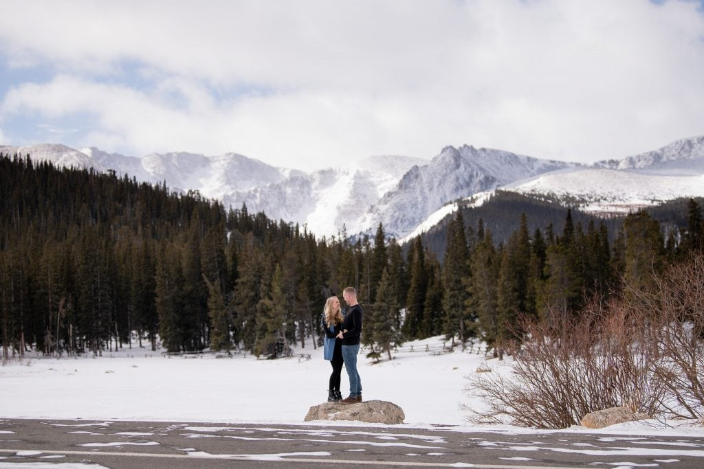 Newly engaged couple embracing each other in front of a frozen lake, mountains, and trees in Colorado