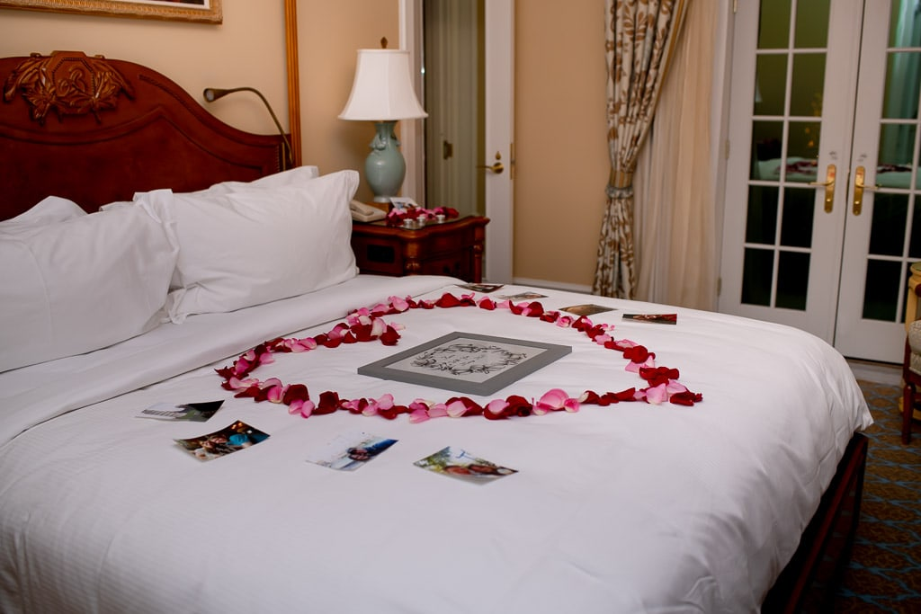 Proposal setup in a hotel room with rose petals in the shape of a heart on the bed with photos of the couple and a framed drawing in the center