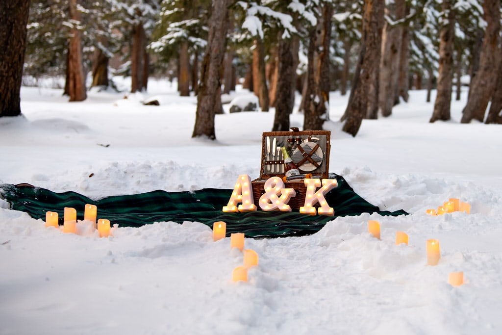 Proposal setup in the snowy woods of Colorado with a picnic on a blanket and electric candles and light up letters 'A' & 'K'