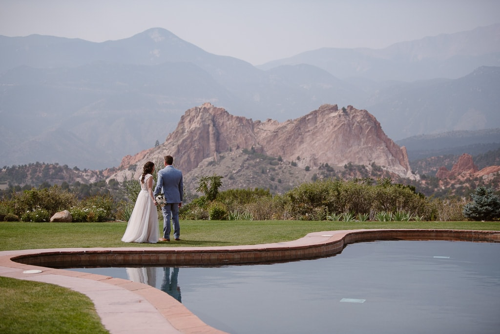 Bride and groom holding hands by a reflecting pool at Garden of the Gods Resort in Colorado Springs