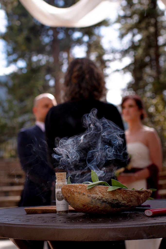 Bowl of burning sage at a commitment ceremony with officiant, bride, and groom in the background