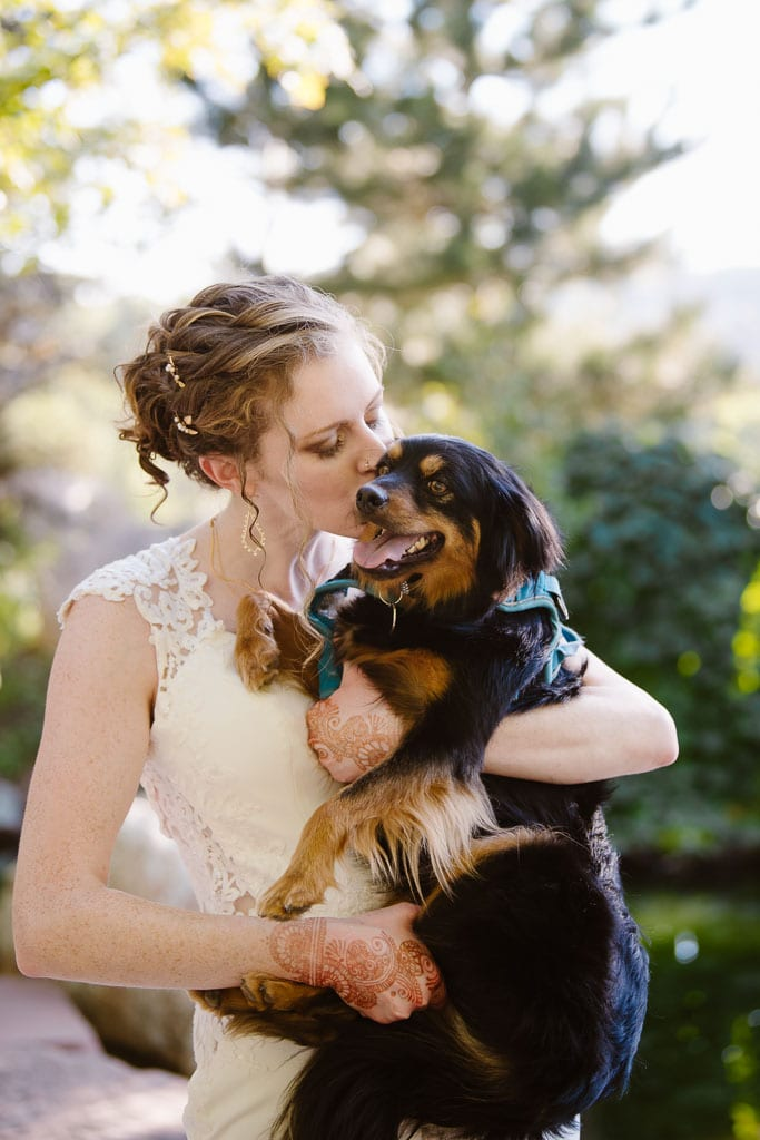 Bride with blonde curly hair and henna tattoos holds and gives a kiss to a small black and brown dog