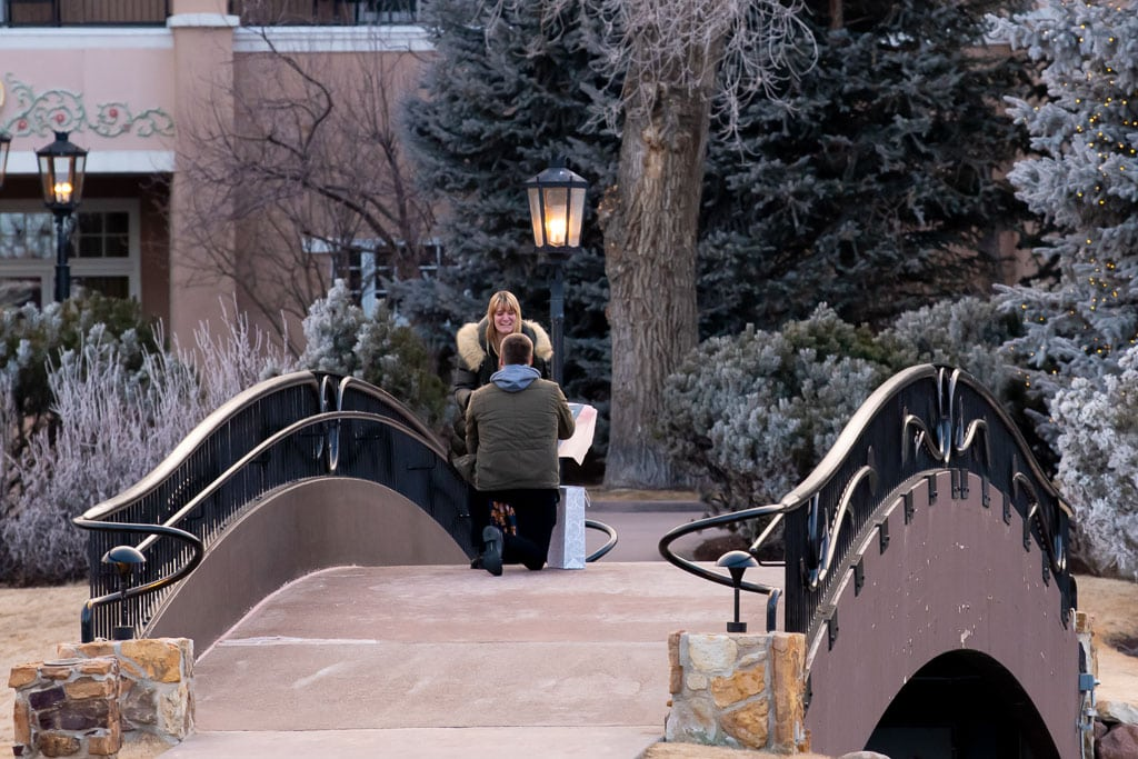 Man on one knee proposing to a blonde woman on the bridge at The Broadmoor hotel in Colorado Springs