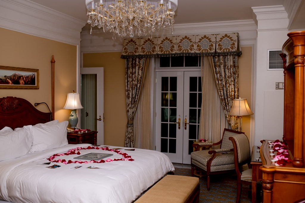 Ornate hotel room with yellow walls, a chandelier, lamps, and white french style doors, with a heart shape of rose petals on the bed
