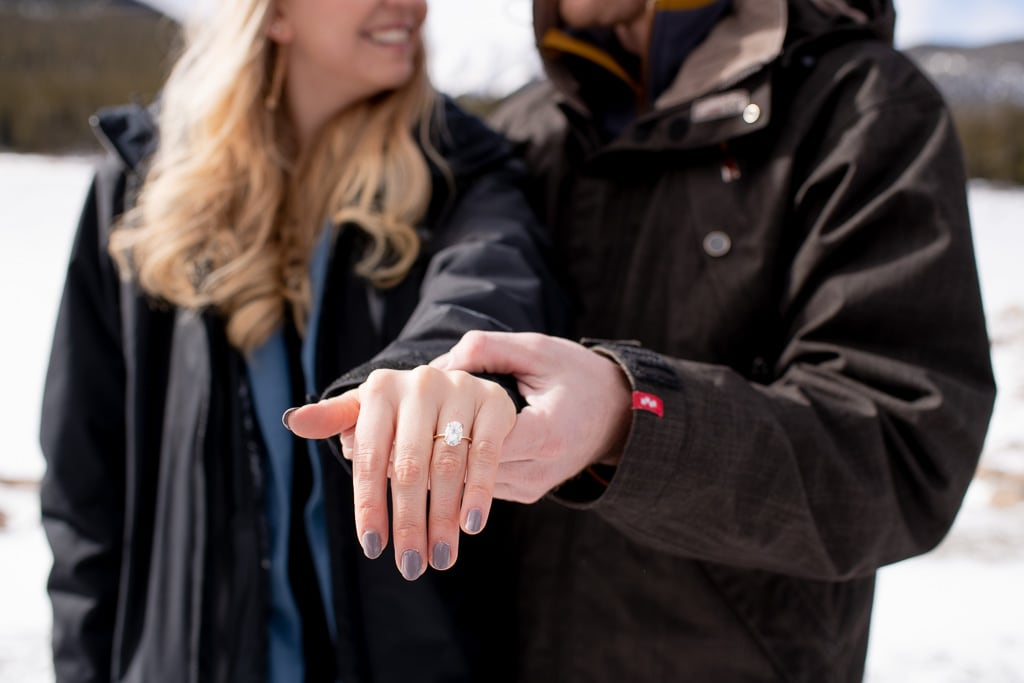 Man holding out woman's hand that has an engagement ring on it