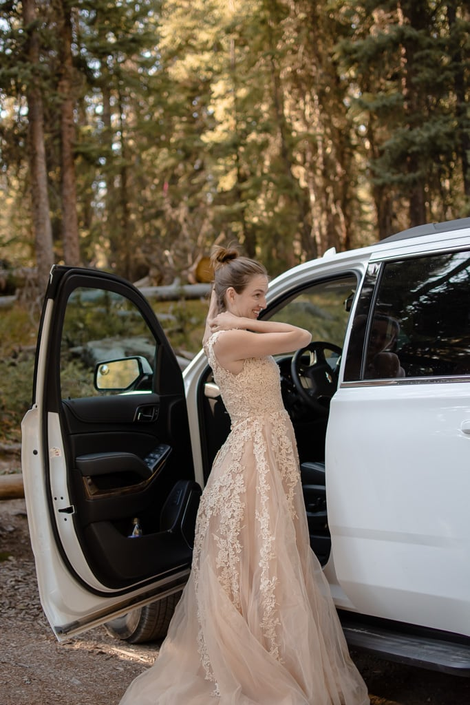 Bride getting her dress on near her white SUV at a wooded trailhead near Vail, CO