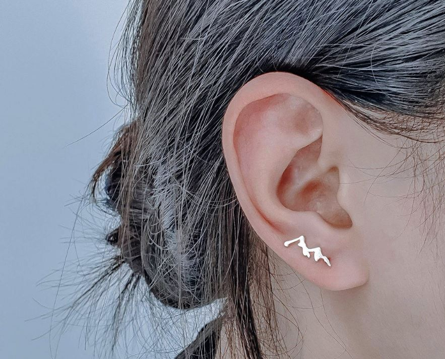 White woman with grey hair wearing a small mountain stud earring