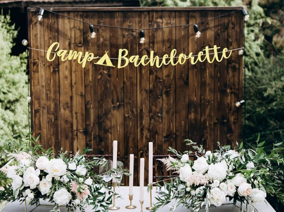 Camp Bachelorette sign in gold lettering in front of a rustic wooden background