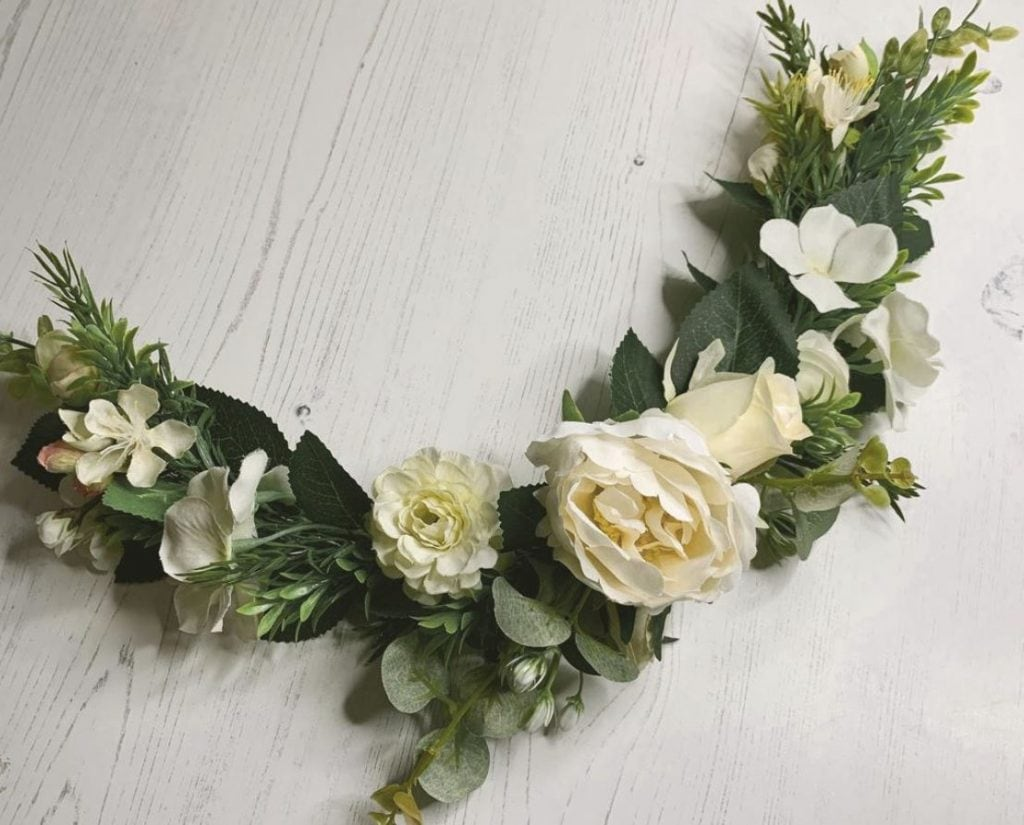 Flower collar for a dog with white flowers and greenery, laying on a white wooden table