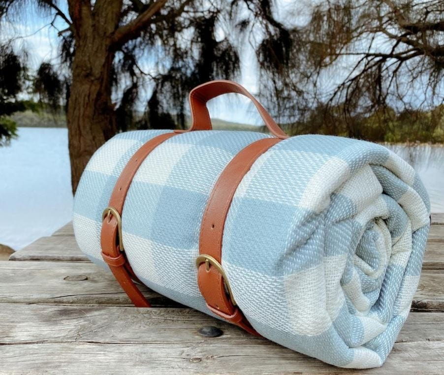 Baby blue and white checkered picnic blanket rolled up sitting on a wooden table