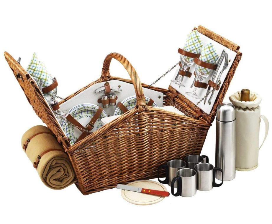 Wicker picnic basket with plates, utensils, and cups inside with a blanket on the side