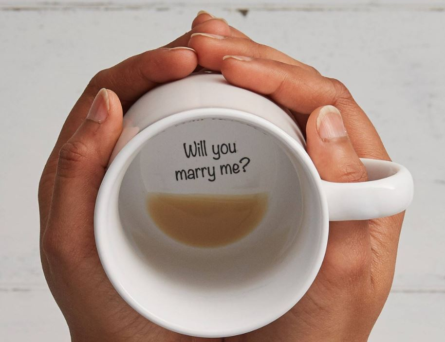 White coffee mug held in hands with a Will You Marry Me? message at the bottom
