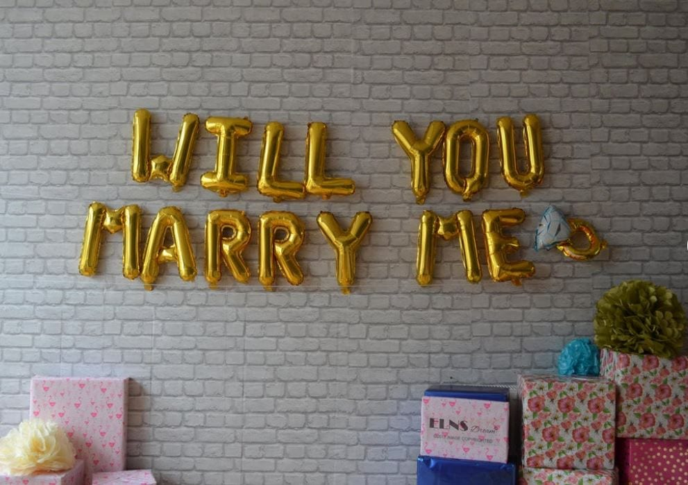 White brick wall with gold balloon letters that say Will You Marry Me?