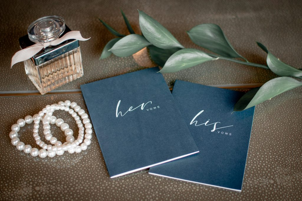 His and Hers Vow books, three pearl bracelets, a bottle of Chloe perfume, and some greenery sitting on a table