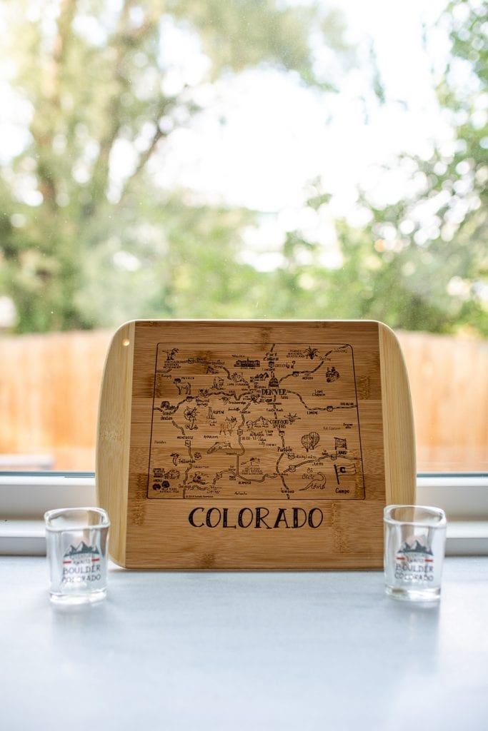 Wooden cutting board with a map of Colorado carved into it sitting on a shelf in front of a window next to two shot glasses
