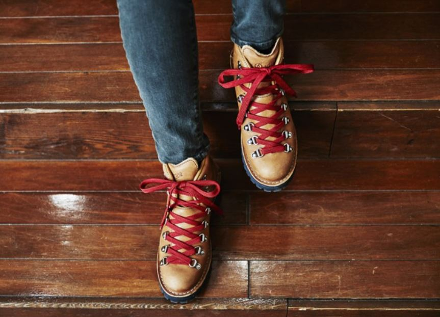 Brown leather Danner hiking boots with flat red laces worn by a girl in skinny jeans with a wooden floor background