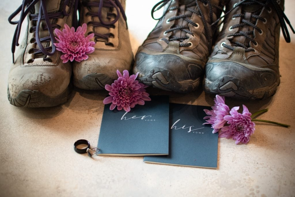 A pair of men's and women's hiking boots showing wear and tear are next to each other on a marble table with flowers, vow books, and rings