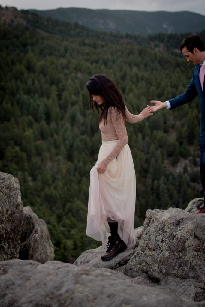 Bride walking on rocky terrain and holding up her wedding skirt showing hiking boots