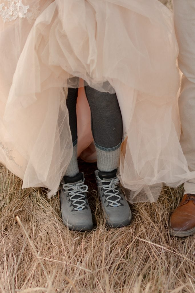 Bride standing in tall grass holding up her dress showing hiking boots and grey leggings