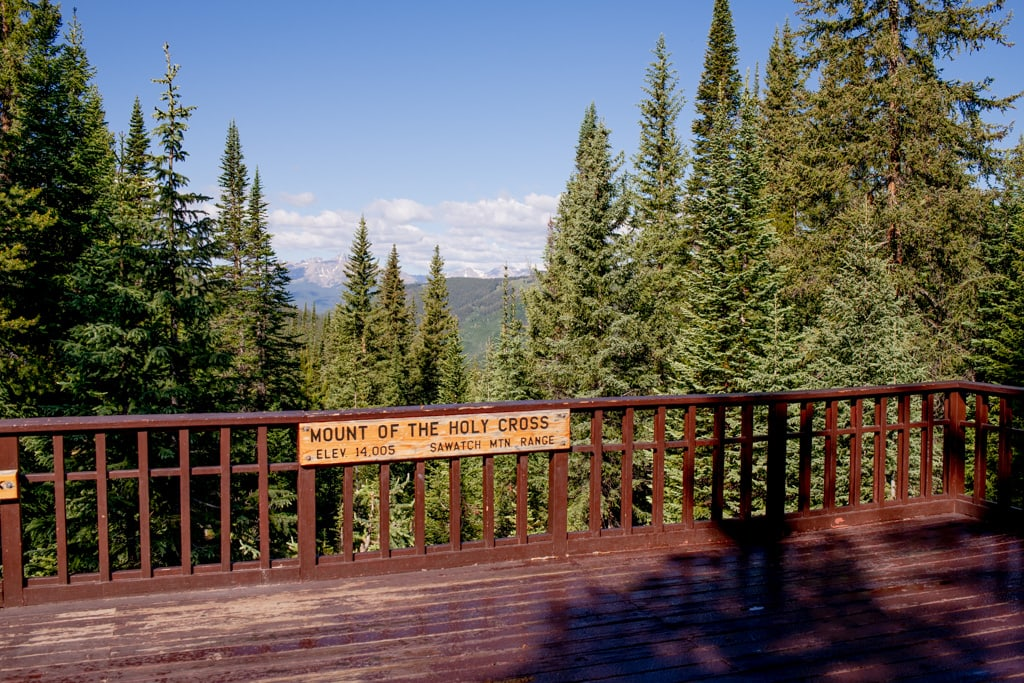 Julia's Deck on Shrine Pass with a brown wooden deck with mountain views and a sign that says Mount of the Holy Cross