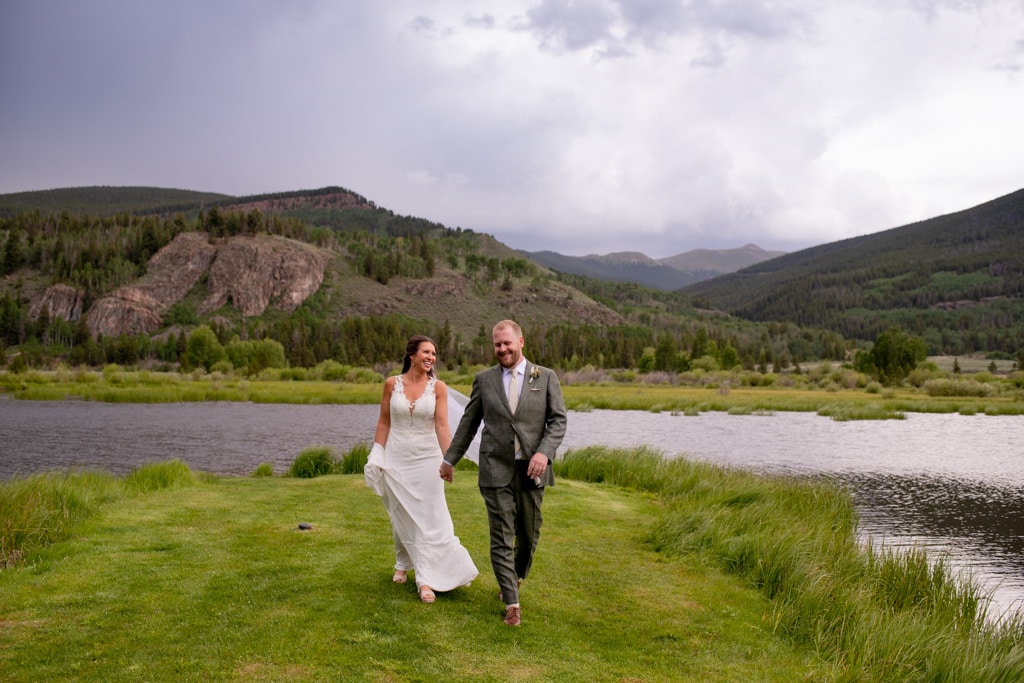 Bride and groom getting married in front of a lake with mountain views near Vail Colorado