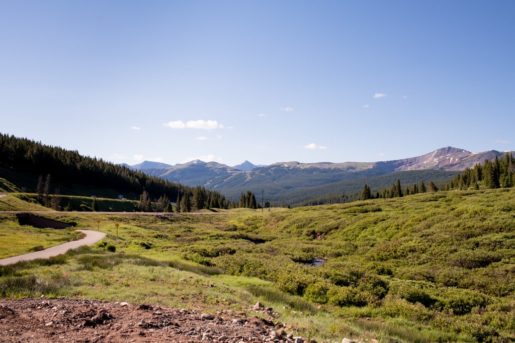 Landscape photo of Vail Pass elopement location with green grass and mountains on a sunny day