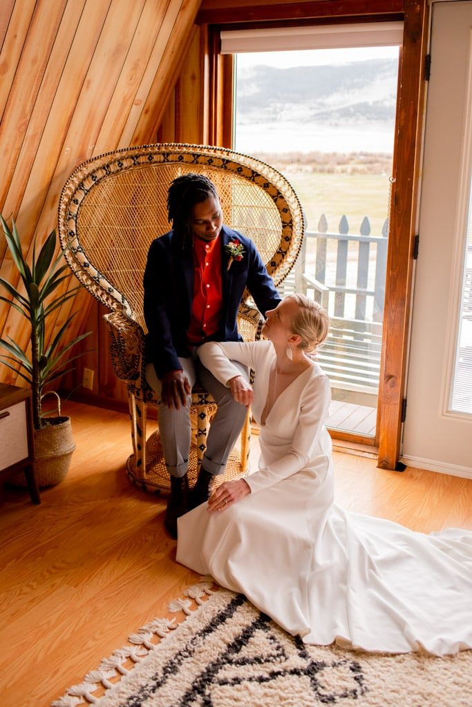 Lesbian bride and bride sitting in their Airbnb on a wicker chair and rug floor before their Colorado Airbnb elopement