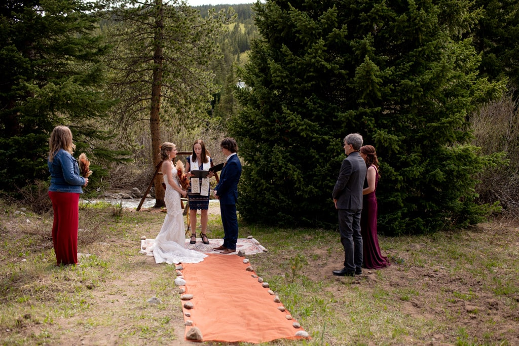 Bride and groom get married by an officiant with parents watching in an Airbnb backyard with trees in Colorado