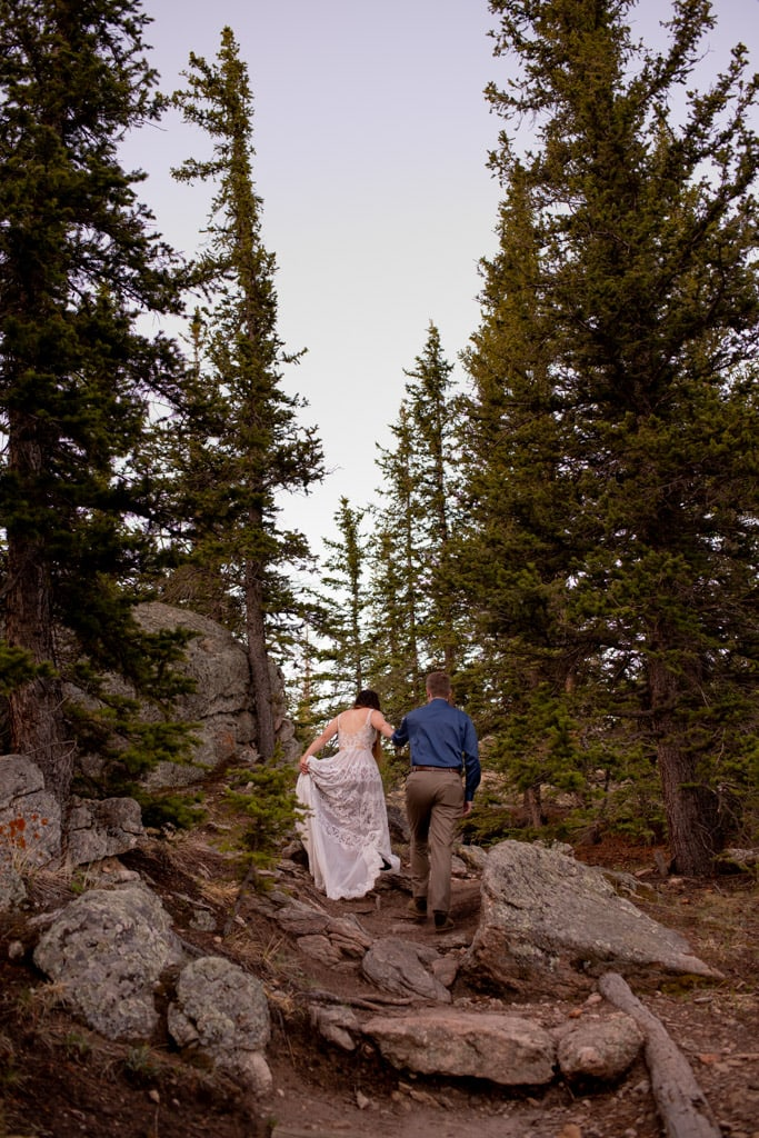 Bride and groom hiking up a rocky trail in Colorado surrounded by evergreen trees