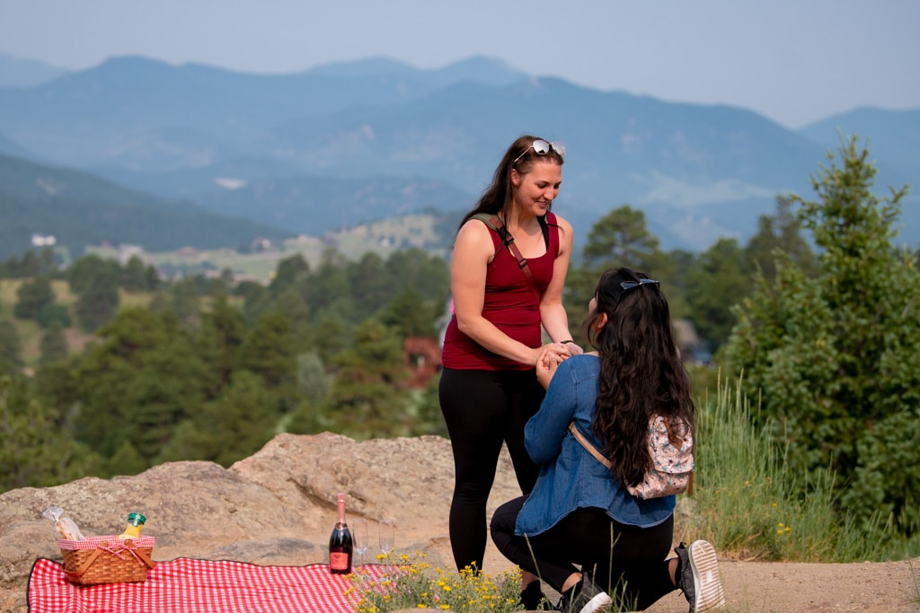 Woman proposing to another woman in front of a picnic in Colorado for same sex LGBT mountain proposal